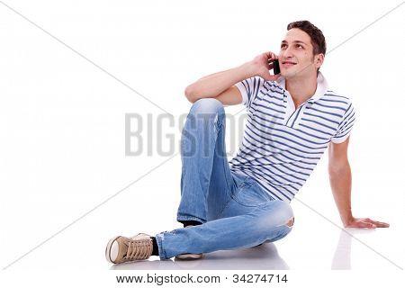 joven casual hablar por teléfono mientras se está acostado en el piso