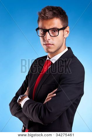 Portrait of a handsome serious young business man in suit over white background