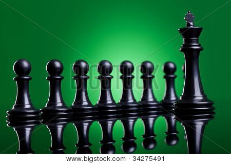 the leader and his team - black king standing in front of his black pawns
