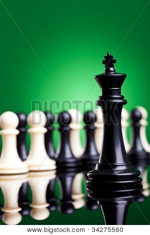 black king standing in front of all the pawns, black and white, on green background - closeup picture