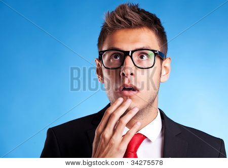 Astonished business man looking up at something on blue background