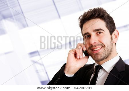 Young smiling businessman calling on phone at office