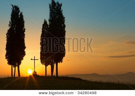 Sunrise behind a lonely cross between cypress trees on the rolling hills of Tuscany near Pienza Italy