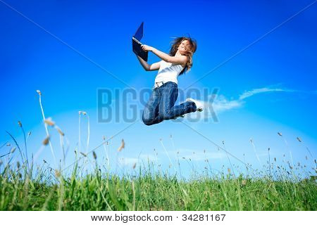 Woman holding a laptop computer jumping over blue sky