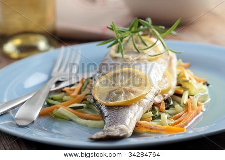 Baked sea bass on a bed of roasted vegetables