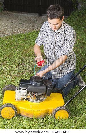 Man repairing yellow lawn mower