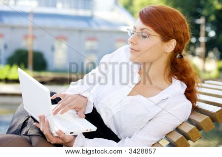 Businesswoman With Laptop In The Park