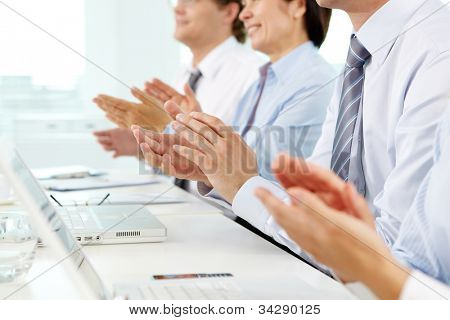 Business people sitting in a row applauding cheerfully to their successful colleague