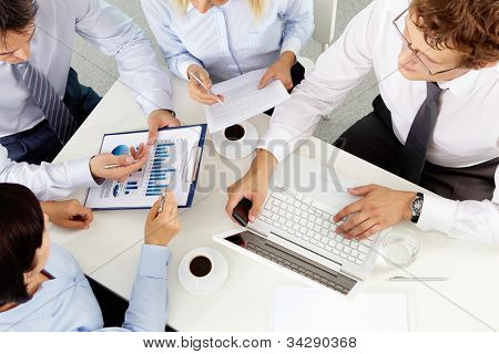 Business leader taking a close look at the charts and graphs at the meeting