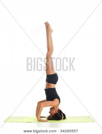 Sporty woman standing on her head isolated on white