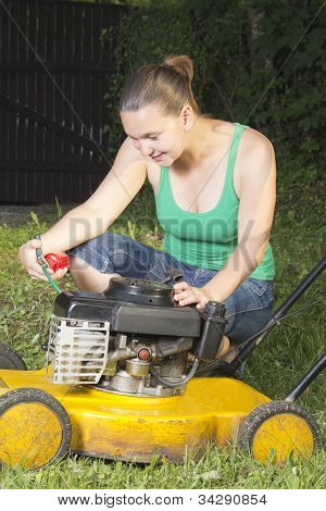 Cute girl oiling yellow lawn mower