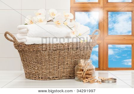 Basket of freshly laundered towels in sunlit kitchen window