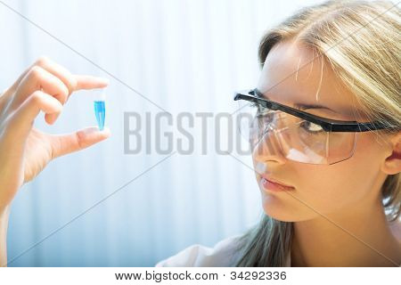 young woman holding a plastic test tube
