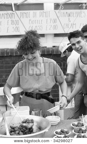 LONDON - JULY 21: A woman ladles strawberries at the Italian street party in Warner Street, Clerkenwell on July 21, 1990 in London. The event follows the annual procession of St.Mary of Carmel.