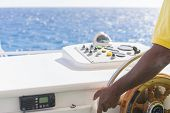 Hand Of Captain On Steering Wheel Of Motor Boat In The Blue Ocean During The Fishery Day. Boat Or Ya poster