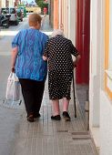 picture of old lady  - Lady helping old Spanish woman walk down street with stick.