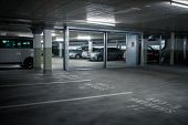 Gated underground parking. Cars parked in a garage with no people. Many cars in parking garage inter poster