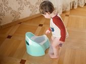 The Boy And The Potty. Adorable Baby Girl Playing With A Chamber Pot At The Living Room. Adorable Ba poster