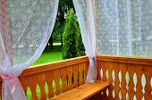 stock photo of lace-curtain  - Wooden porch with lace curtains and garden view - JPG