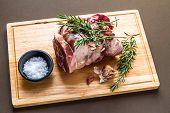 Raw Rolled And Tied Herdwick Sheep Lamb Joint Prepared With Garlic, Rosemary And Sea Salt. poster