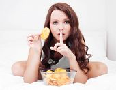 stock photo of fat lip  - pretty woman eating potato chips in bed at home with finger on her lips - JPG