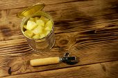 Opened Tin Can Of Pineapple Pieces And Can Opener On Wooden Table poster
