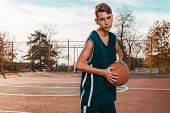 Sports And Basketball. A Young Teenager In A Blue Tracksuit Poses With A Basketball In His Hands. In poster