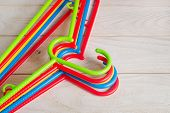 New Multicolored Plastic Clothes Hangers On A Light Wooden Surface. Set Of Five Colorful Plastic Clo poster