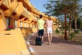 Young Couple Standing At Hotel Upon Arrival, Looking For Room, Holding Suitcases poster