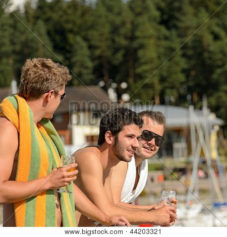 Young guys holding glasses talking at beach