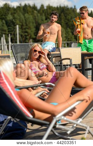 Young women sunbathing on deckchair and guys drinking beer