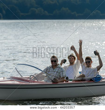Cheerful young men party drinking beer on speed boat