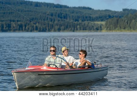 Young men sitting in motorboat in scenic landscape