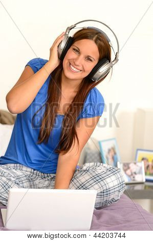 Cheerful teenager girl listening music with headphones on laptop