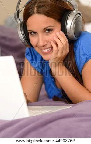 Young smiling girl using laptop and listening music with headphones