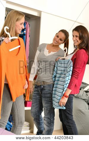 Three teenager girl friends choosing clothes from closet together