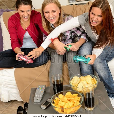 Laughing teenage girls playing with video game with consoles