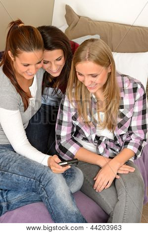 Young teenager girls looking at pictures on digital camera