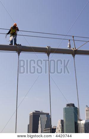 Worker On Top Of Brooklyn Bridge In New York City