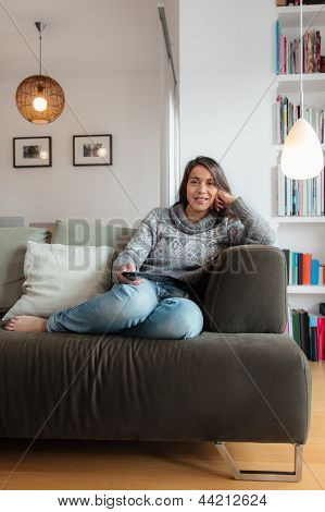 Young Woman Watching Tv Home In Sofa