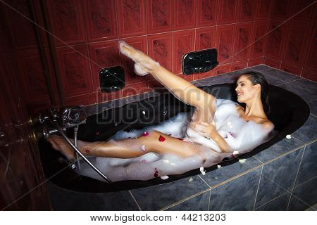Beautiful woman relaxing in black tub with foam
