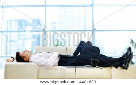 Businessman Resting On Sofa