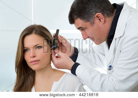 Doctor ENT checking ear with otoscope to woman patient at hospital
