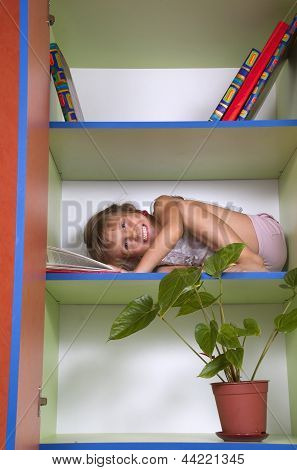 Smiling Little Girl Reading A Book In A Bookcase