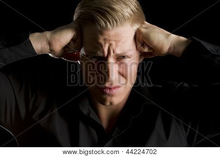 Low-key portrait of young frustrated man in dark shirt with fists at temples and looking straight, isolated on black background.