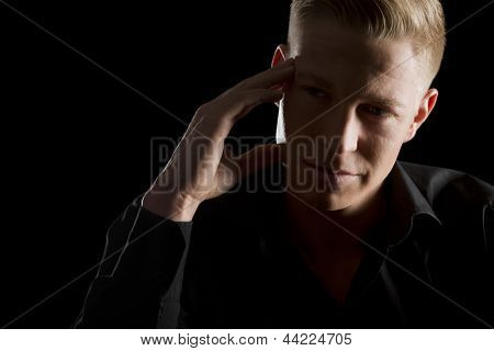 Low-key portrait of young charming man with hand at temple looking aside, isolated on black background.
