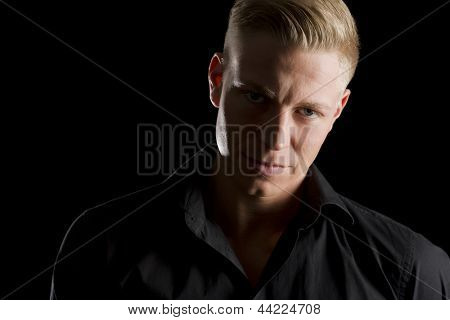 Low-key portrait of young attractive  man in dark shirt looking straight, isolated on black background.