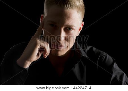 Low-key close up portrait of young seductive man in dark shirt looking straight, isolated on black background.