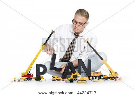 Build up a plan concept: Attentive businessman building the word plan along with construction machines, isolated on white background.