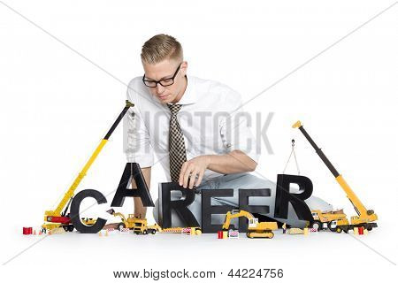 Build up career concept: Focused businessman building the word career along with construction machines, isolated on white background.
